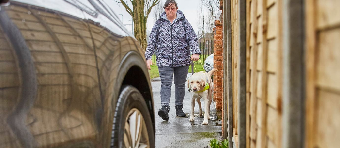 A guide dog owner and her dog walk towards a pavement parked car which they will not be able to pass