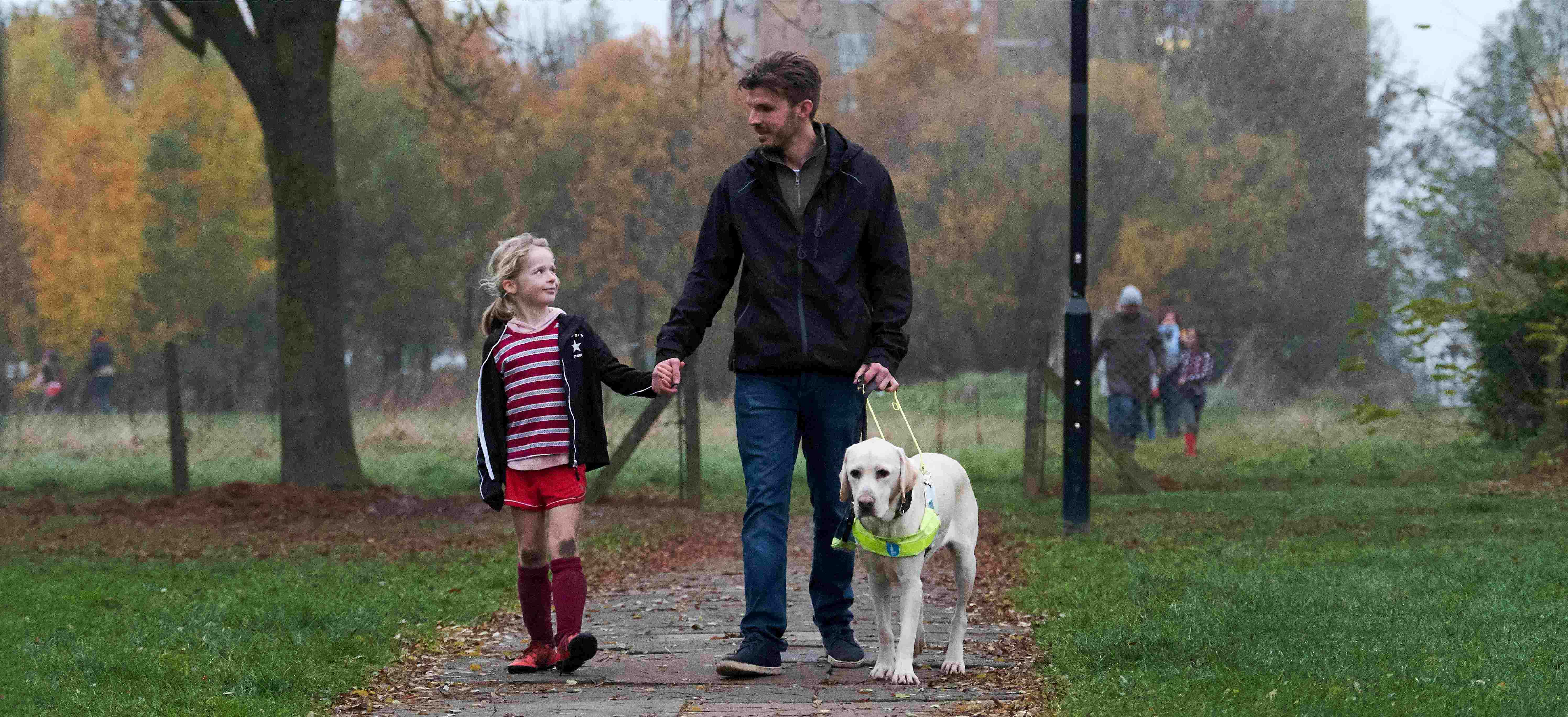 Alex walks down a park path with his guide dog and daughter who is wearing a football kit with muddy knees. They smile at eachother.