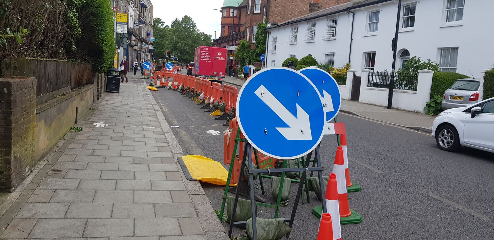 An image of a pavement that has been extended into a road with cones separately the two areas