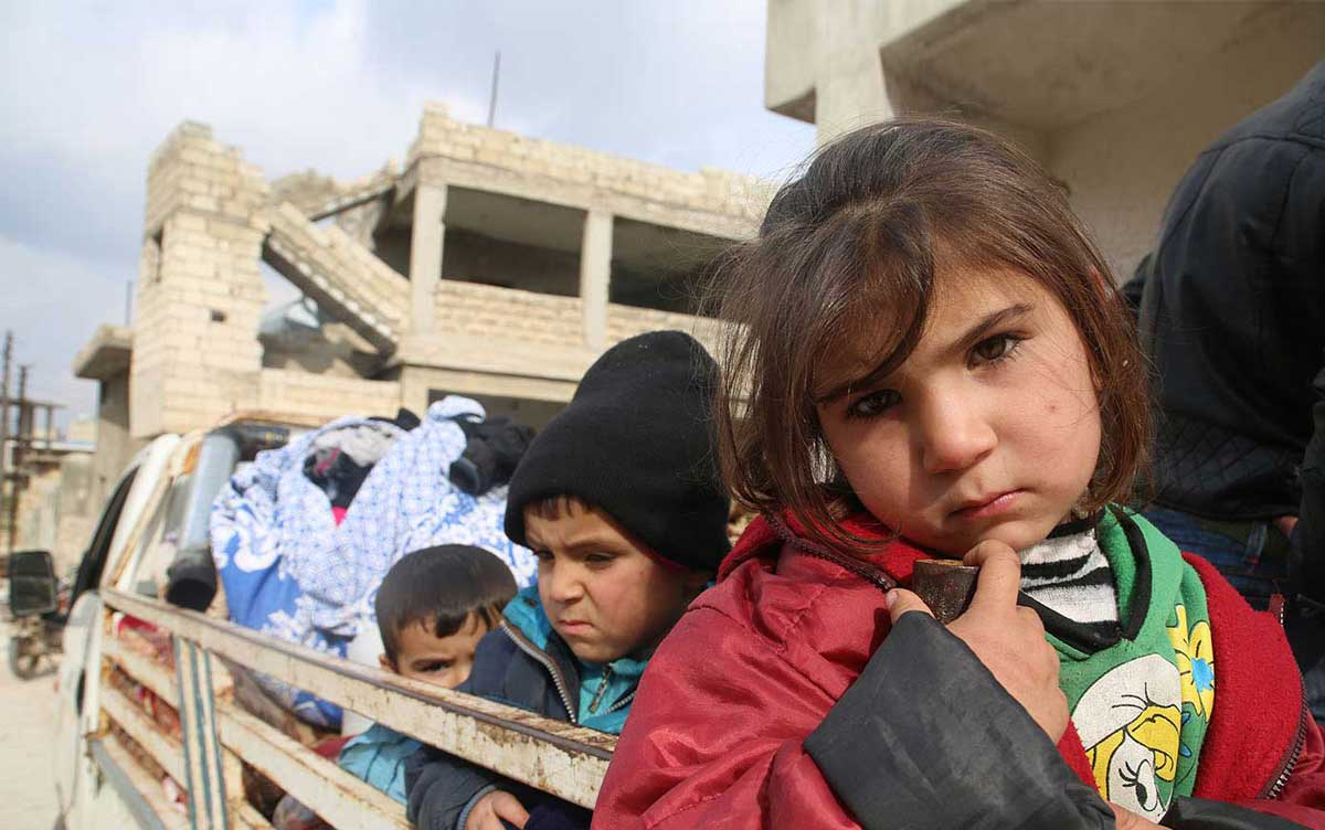 Children ride in the back of a truck as families flee from Saraqeb and Ariha in south rural Idlib, Syria.