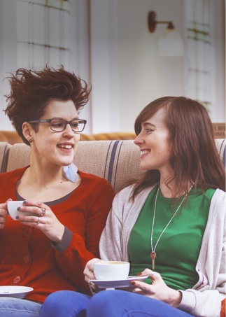 Two women sit talking over coffee