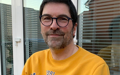 Martin wearing a yellow top and glasses smiling to camera