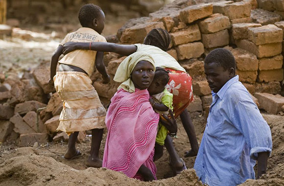 A family comes out from a foxhole where they hid when 12 bombs were dropped in Kauda town, destroying three houses, and injuring one man in Southern Kordofan, Sudan.
