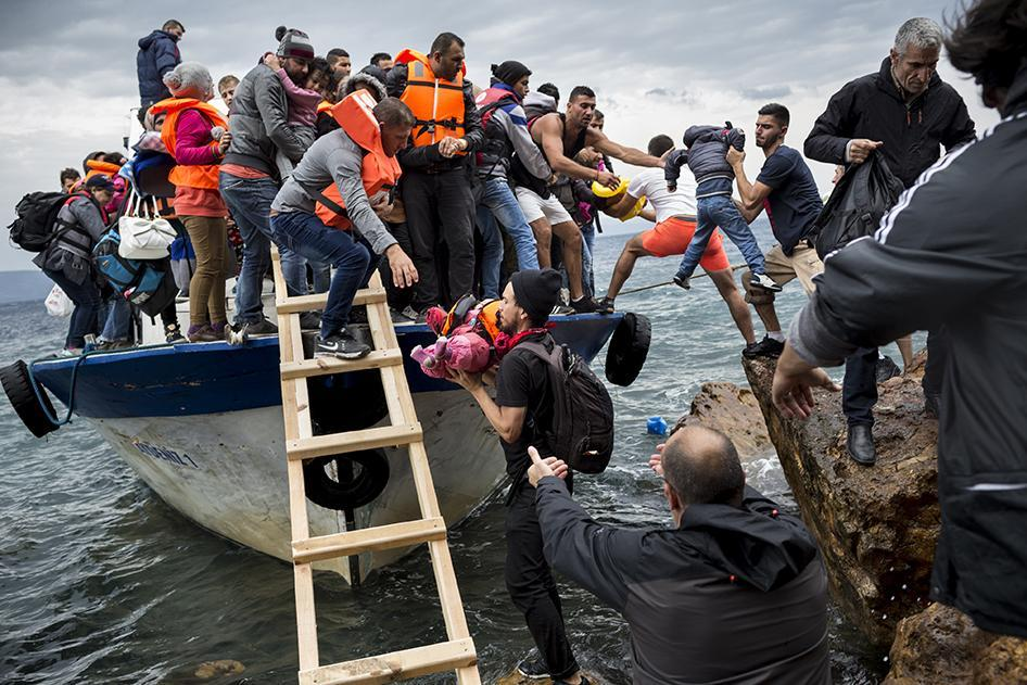 Asylum seekers and migrants descend from a large fishing vessel used to transport them from Turkey to the Greek island of Lesbos. October 11, 2015.  © 2015 Zalmaï for Human Rights Watch