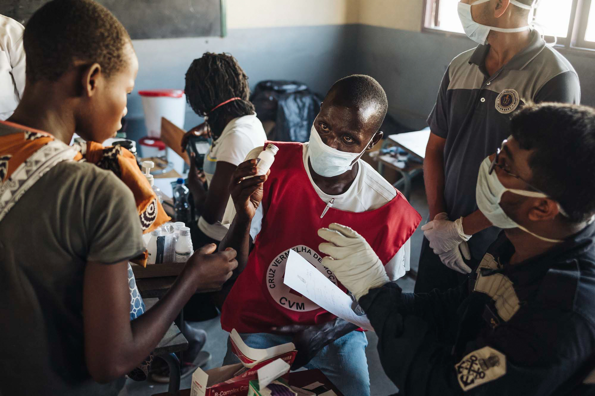 A Red Cross Support worker administers medical aid to those affected by Cyclone Idai inside of a small pop-up aid center.