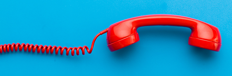 Red corded phone on a blue background