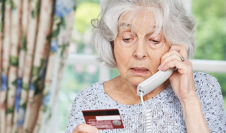 Elderly woman on the phone holding a credit card.