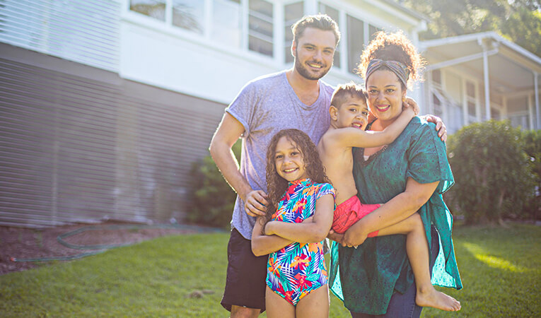 Family standing in front of their home – renting campaign lead.
